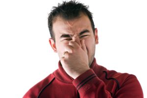 Man with allergy holding his nose